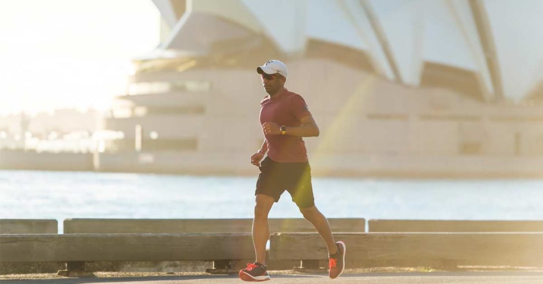 Man running along a harbor with Sydney Opera House in background